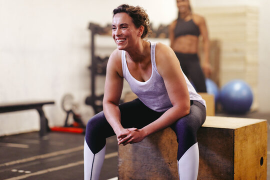Smiling woman sitting on a box after a gym workout