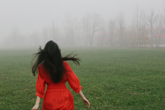 Girl in red dress escapes into the fog