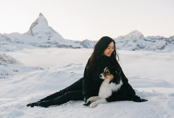 Girl with dark hair in black clothes sitting with dog against the backdrop of a mountain landscape
