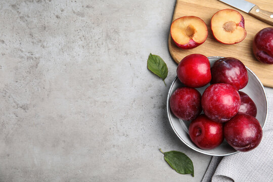 Delicious ripe plums on grey table, flat lay. Space for text
