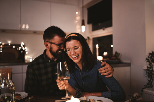 Couple laughing over glasses of wine during a candlelit dinner party