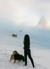 Unrecognizable girl with dark hair in black clothes stands with dog against the backdrop of a mountain landscape