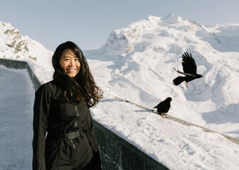 Beautiful asian girl with dark hair in black clothes stands against the backdrop of a mountain landscape