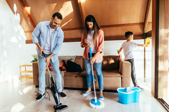 Latin family cleaning the house together