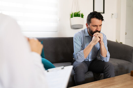 Sad man discussing his psychological issues with a psychiatrist