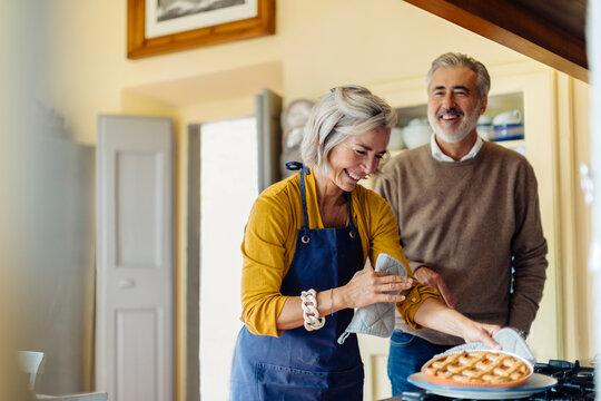 Mature couple laughing at joke in kitchen