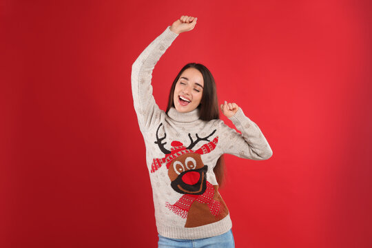 Young woman in Christmas sweater on red background