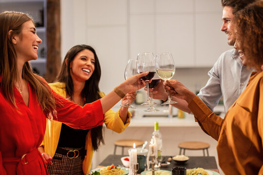 Friends standing at table and toasting with wine