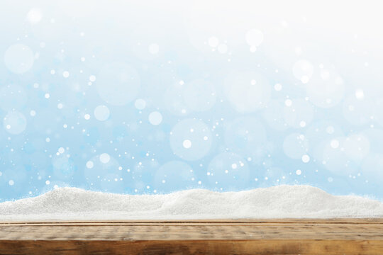 Wooden surface with snow against light blue background, bokeh effect