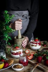 Chef cooking tasty dessert with fresh berries in dark kitchen