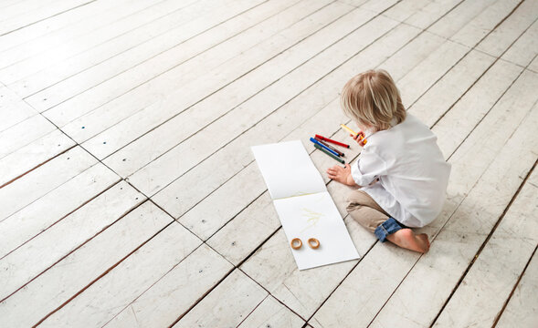 A little boy draws on the floor.