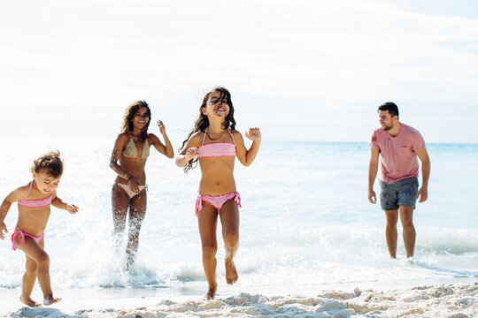 Happy multiracial family enjoying summer holidays on seashore