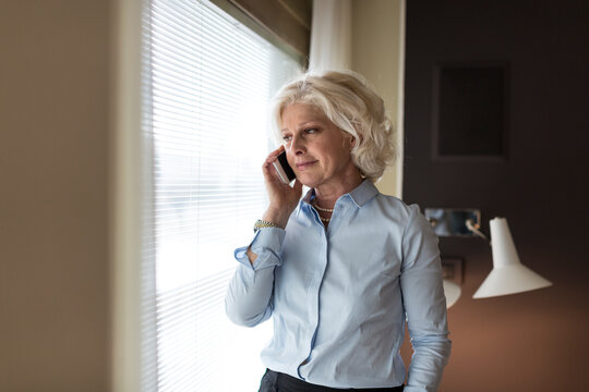 Elegant middle aged woman speaking on phone in hotel room