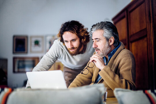 Adult son teaching senior father to use laptop