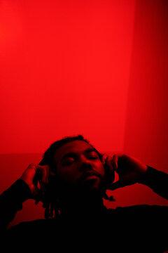 Bearded guy listening to music in red light