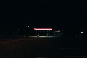 Bright gas station glowing in darkness of night Fotomurales