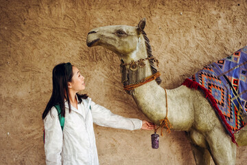 Young woman with camel on street