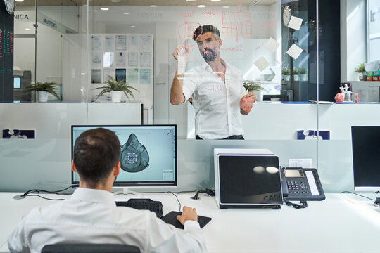 Mature worker analyzing data on glass wall in clinic