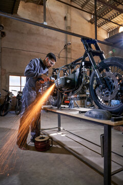 Male worker grinding parts of motorcycle