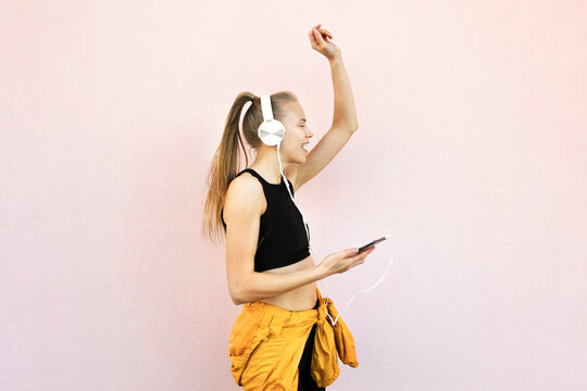 Young woman listening to music on the phone and dancing isolated on bright background