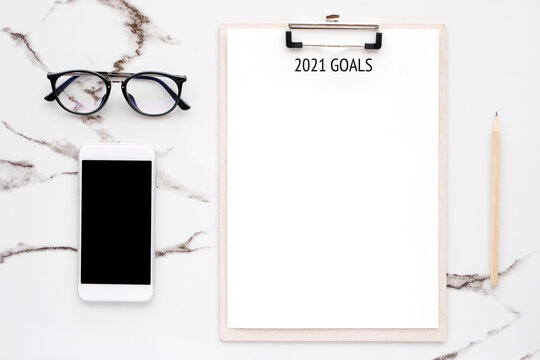 2021 goals on blank note paper with copy space for text and smartphone with blank screen on white marble background, new year aim to success in business background