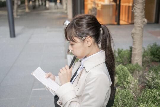屋外でメモを取る女性
