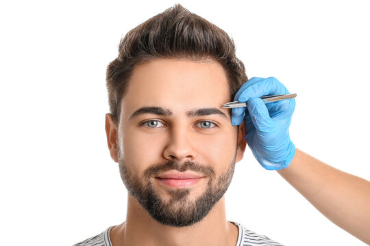 Young man undergoing eyebrow correction procedure on white background