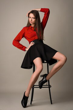 beautiful slender model in a black skirt and red shirt posing sitting on a bar stool in the studio