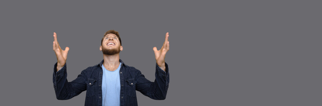 Caucasian man is looking up and thanking god for something while posing on a gray studio wall with free space
