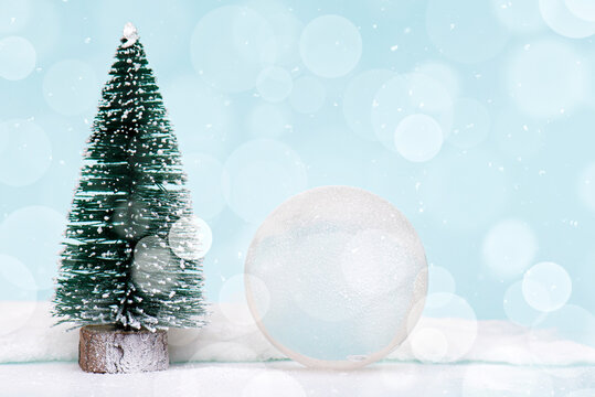 Christmas or New Year composition, decoration with glass ball snow globe and fir tree covered by snow on glitter background