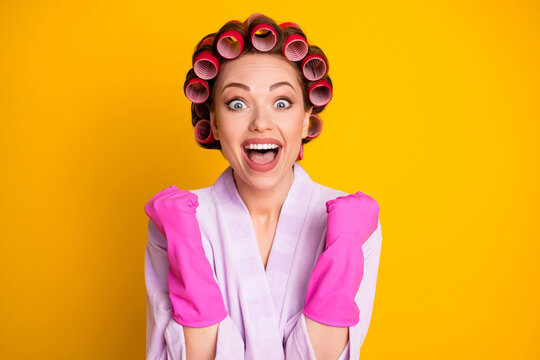 Close-up portrait of lovely overjoyed cheerful housekeeper wearing curlers celebrating great news isolated bright yellow color background