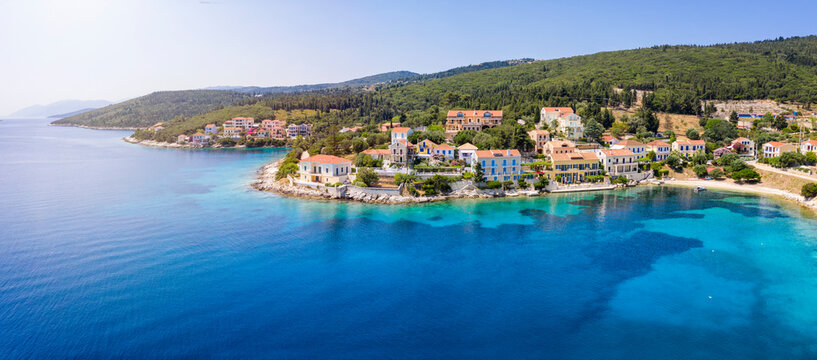 Panoramic aerial view to the beautiful village of Fiskardo on the island of Kefalonia, Greece, with colorful, red roofed houses by the turquoise sea