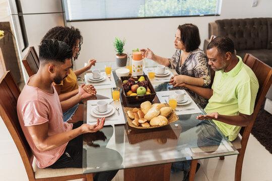 Latin American family having breakfast at home. family praying before eating