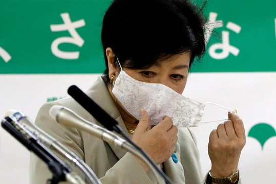 Tokyo Governor Yuriko Koike takes off her mask during a news conference on city's response to the coronavirus disease (COVID-19) outbreak, in Tokyo