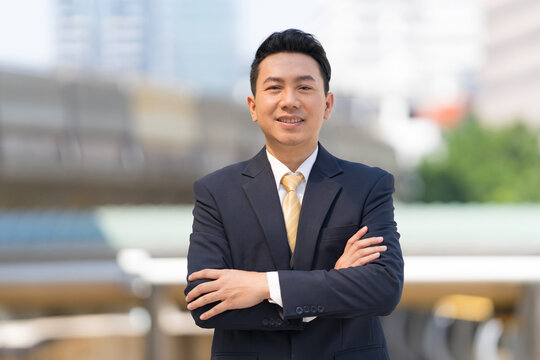 Portrait of successful businessman standing with arms crossed standing in front of modern office