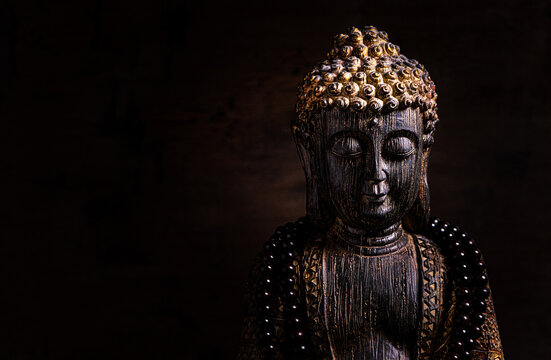 Close up of a statue of Buddha with singing bowl and prayer beads (mala) for chanting mantras as decoration on an old wooden board - yoga