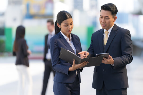 Mature businessman using a digital tablet to discuss information with businesswoman