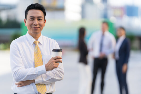 Portrait of smiling businessman holding a coffee cup while standing