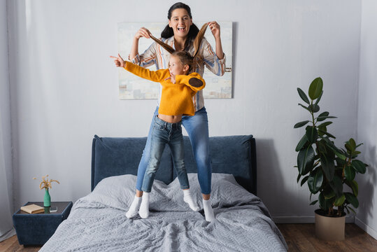excited mother holding hair of daughter while she pointing with finger and jumping on bed