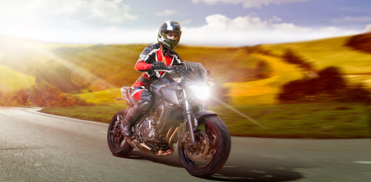 female motorcyclist riding motorbike on the country road accelerating while leaving the curve to overtake. motion blurring rural country side background. copy space to the right for your advertisement