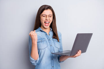 Photo of impressed hooray long hairdo lady hand fist hold laptop wear spectacles blue shirt isolated on grey color background Wall mural