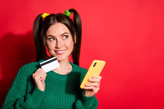 Photo of dreamy young woman dressed green knitted sweater holding phone card looking empty space isolated red color background