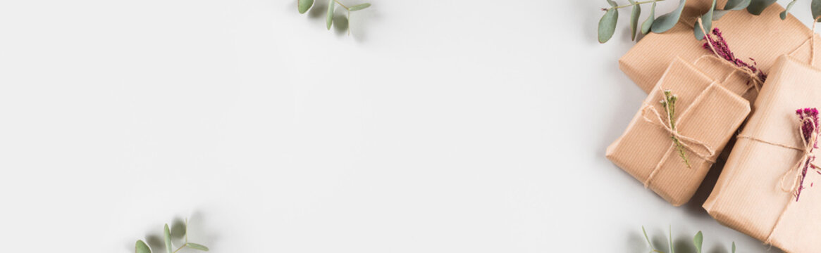 Zero waste holiday gifts wrapped in paper with dried floral decor on gray background. Web banner