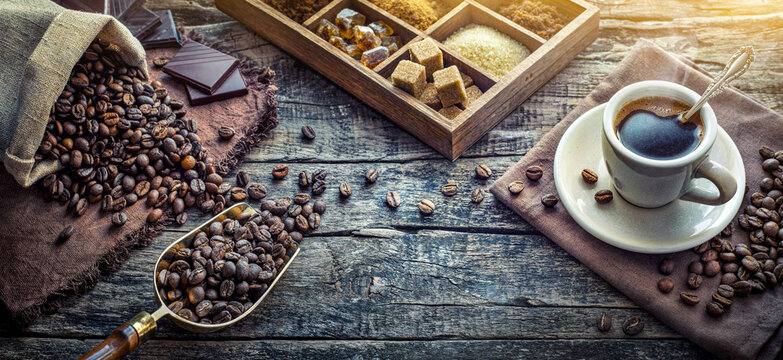 Coffee cup with coffee, coffee beans, cinnamon, star anise on an old wood desk in a coffee shop. Wide image in retro style.