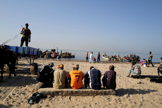 Men sit and watch fishermen's pirogues at the fishing port in Joal