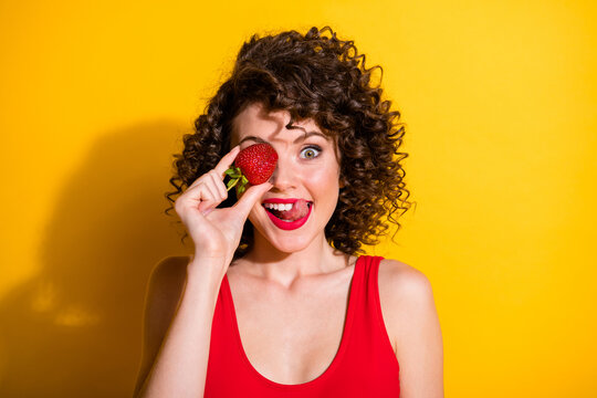 Closeup portrait photo of charming tricky young girl hand hold strawberry cover eye stick out tongue lick lips wear red singlet unclothed shoulders isolated bright yellow color background