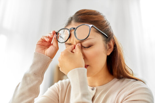fatigue, stress, vision and people concept - tired asian woman with glasses rubbing nose bridge at home