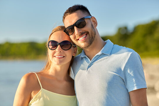 leisure, relationships and people concept - happy couple in sunglasses hugging on summer beach