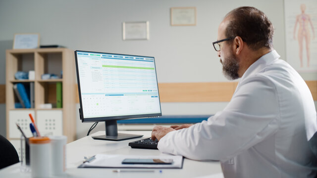 Hispanic Doctors Office: Experienced Physician Sitting at His Desk Working on Personal Computer. Health Care Specialist Filling Medicine Prescription Documents, Checking Analysis Test Results.