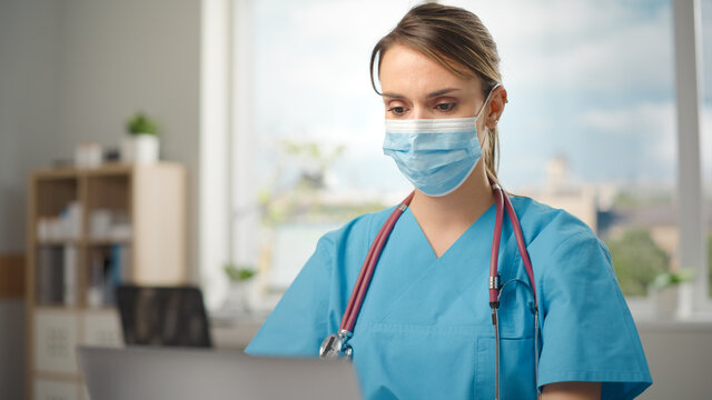 Portrait of Beautiful Hispanic Female Nurse Wearing Protective Face Mask and Focused on Work. Hero of Health Care Industry Working Over the Clock to Cure, Treat and Save People.